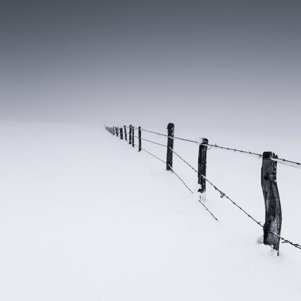 Plot v zasněžené krajině na černobílé fotoografii - Lionel Orriols