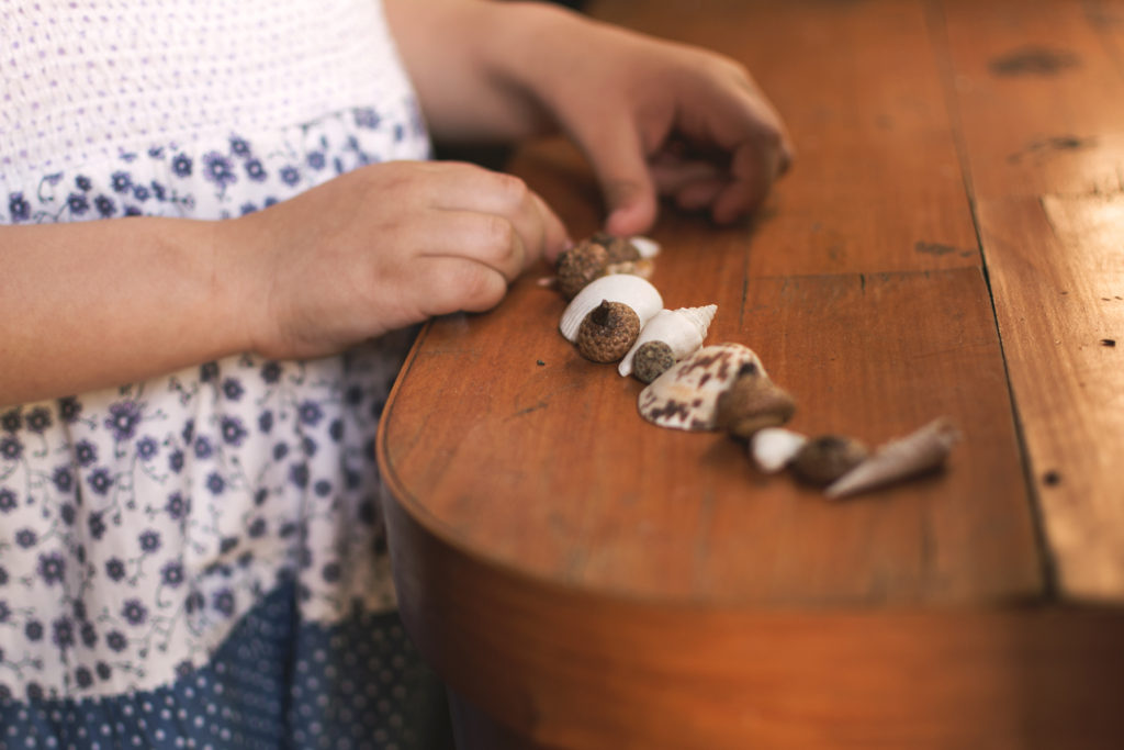 Holčička si hraje s mořskými mušličkami