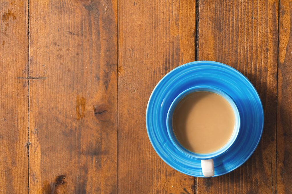 Šálek kávy na dřevěném stole vyfocený z vrchu.
