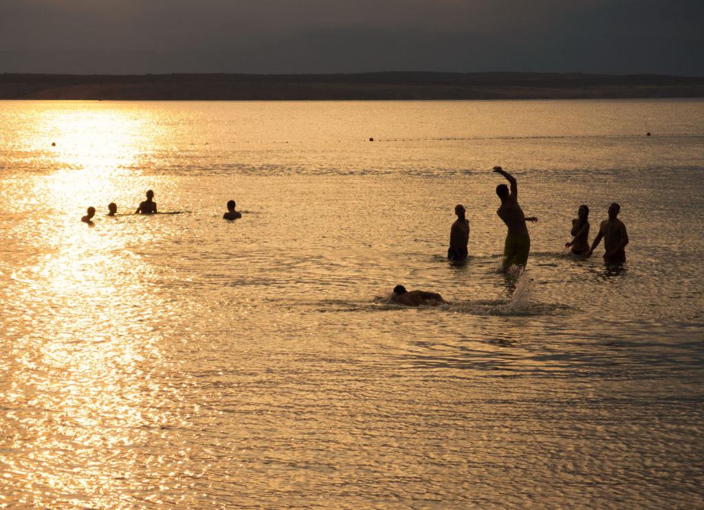 Západ slunce a siluety lidí hrajících si v moři.