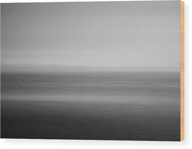 Striktně minimalistická fotografie na dřevěné desce o velikosti 30 x 20 cm.